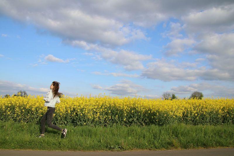 Side view of teenage girl running by oilseed rape field against sky