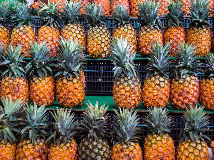 Pineapples arranged on shelf for sale at market stall
