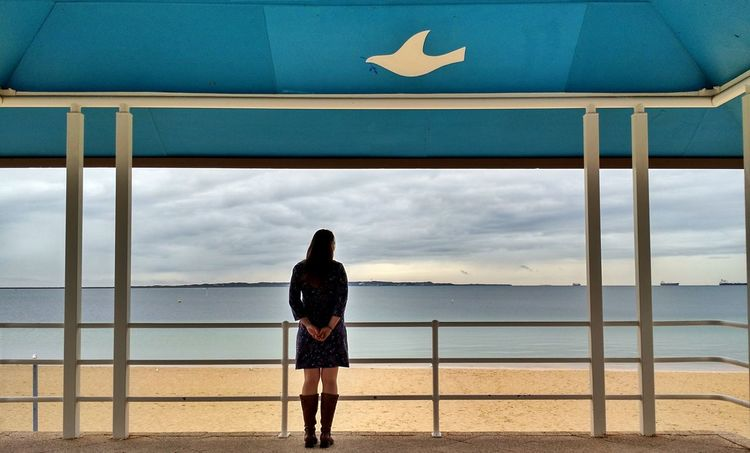 A girl in a dress and boots stands before an empty beach on a gray day. Melancholy Forlorn Alone Beach Overcast Gray Skies Stormy Weather