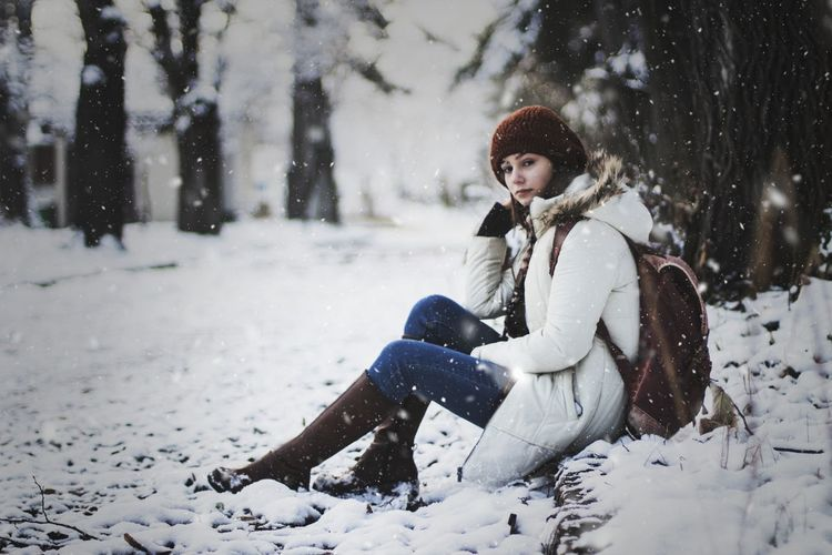 Portrait Of Woman Sitting On Snow Covered Field Against Trees