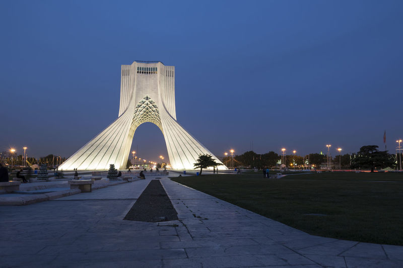 TEHRAN, IRAN - 7 May 2018 Azadi Tower at dusk time formerly known as the Shahyad Tower is a monument located at Azadi square and is an architectural landmark of Tehran Historical Building Architecture Azadi Tower In Tehran Blue Building Exterior Built Structure City Clear Sky Dusk History Illuminated Incidental People Memorial Modern Monument Nature Office Building Exterior Outdoors Sky Skyscraper Tall - High The Past Tourism Travel Travel Destinations