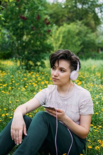 Mid adult woman using mobile phone while sitting outdoors