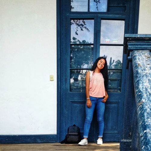 Photographer: @valentinmeidl Blue Door Old Buildings Beautiful Woman Cool Beauty Smile Innocence Fresh Girl Smiling Hair Young Women Full Length Smiling Portrait Doorway Happiness Door Jeans Front View Business Entryway Entrance Front Door Closed