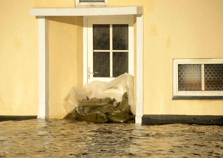 House during a flood siege, the entrance door has been blocked by sandbags. Built Structure Architecture Window No People Building Indoors  Day Garbage Wall - Building Feature Entrance Paper Furniture Bed House Glass - Material Door Reflection Absence Pollution Plastic Bag Storm Surge Flood Sandbags Sky Weather