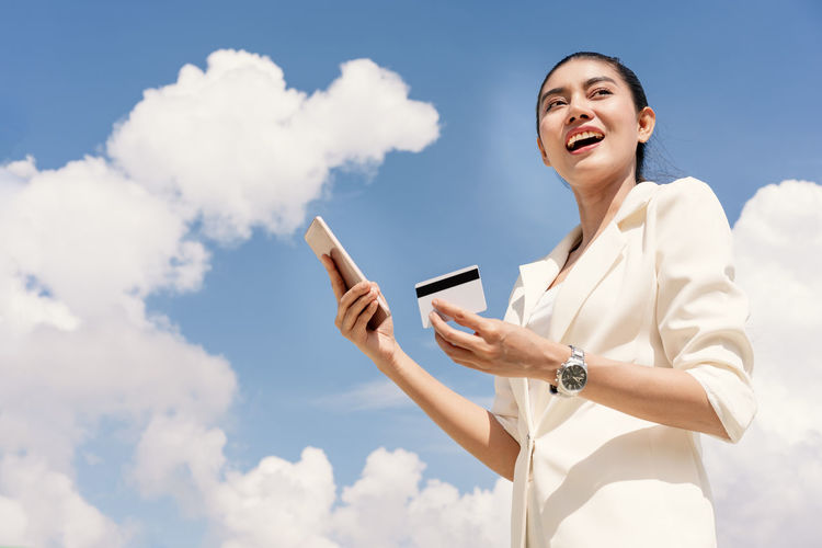Low Angle View Of Smiling Businesswoman With Credit Card Using Phone Against Sky
