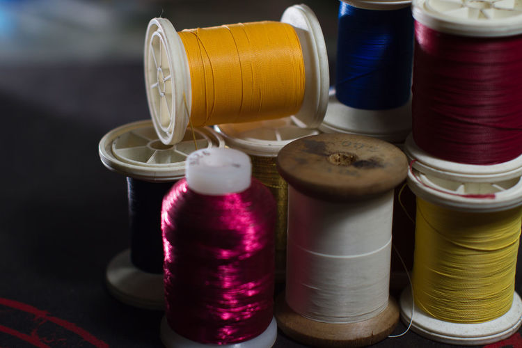 Close-up of multi colored sewing threads on table