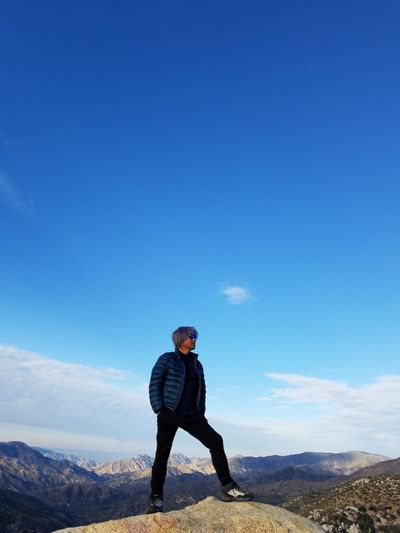 Full length of man standing on mountain against blue sky