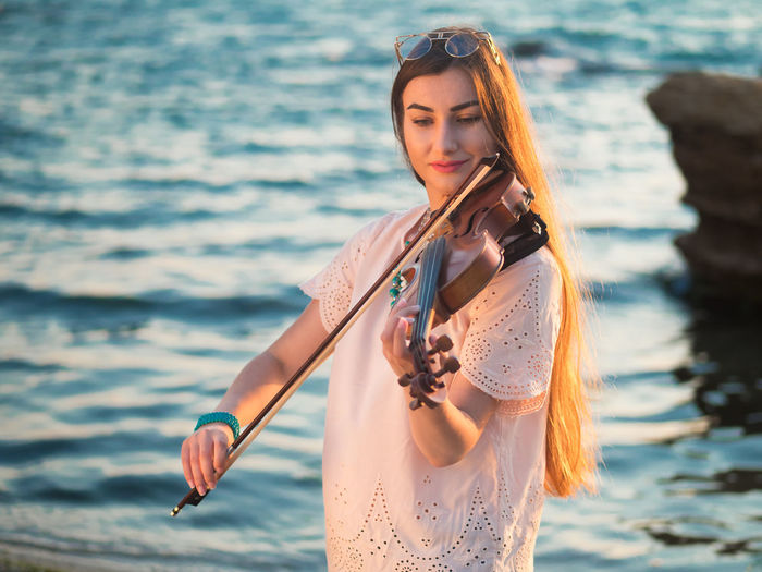 Close-up of young woman playing the violin at seaside