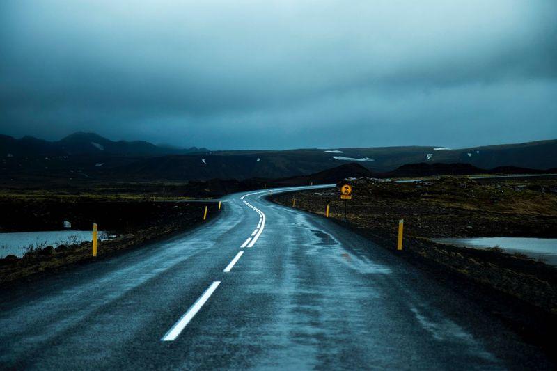 Road passing through landscape during rainy season
