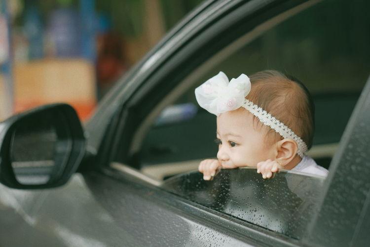 Little baby peek ing outside car window
