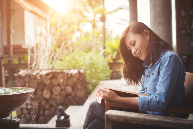 Side view of smiling woman reading book while sitting at yard