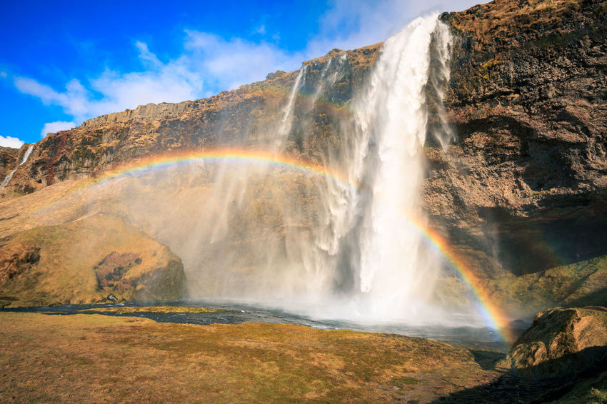 Beauty In Nature Cliff Cloud - Sky Day Iceland Low Angle View Mountain Nature No People Outdoors Power In Nature Rain Rainbow Rock - Object Scenics Seljalandsfoss Sky Sun Tourism Travel Destinations Water Waterfall