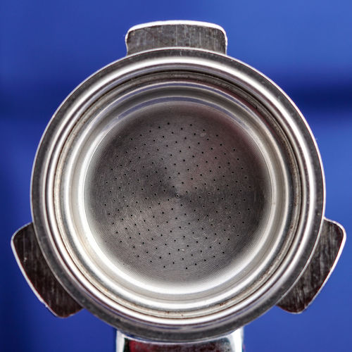 Close-up of portafilter over blue background