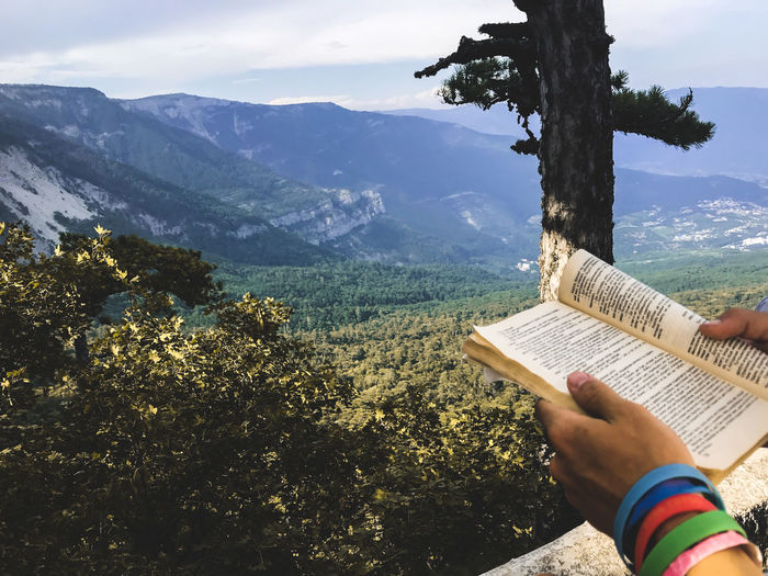 Midsection of person reading book against mountains