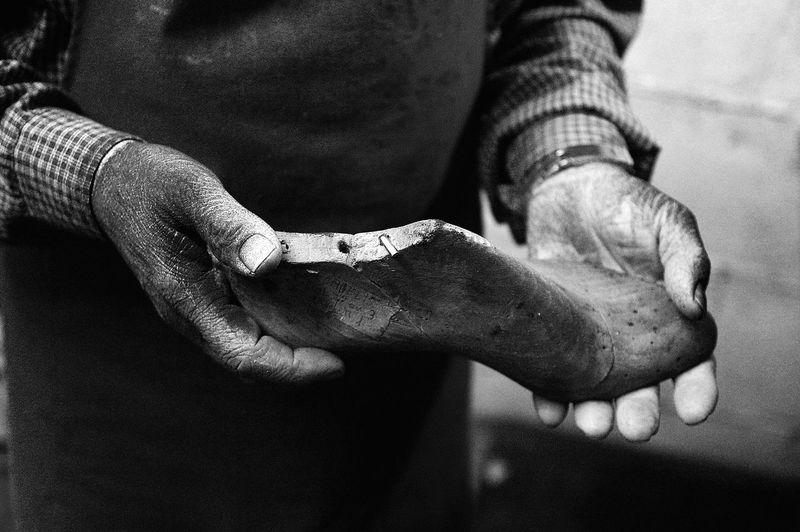 Midsection of shoemaker holding shoe in workshop