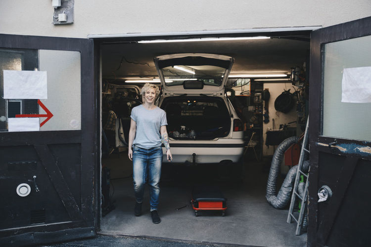 Full length portrait of woman standing in car