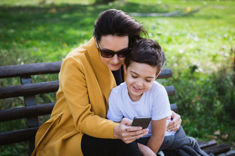 Woman sitting with son at public park