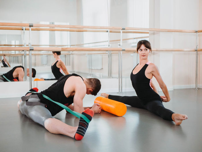 Man And Woman Exercising In Ballet Studio