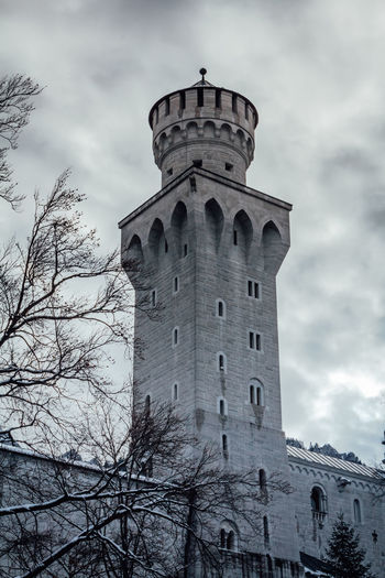 SCHWANGAU, BAVARIA, GERMANY - NOVEMBER 17, 2017: Neuschwanstein Castle in winter landscape. one tower against cloudy sky. Dramatic atmosphere. Bavaria, Germany Sky Architecture Cloud - Sky Building Exterior Built Structure Low Angle View Tree Tower Nature History The Past Day Building Bare Tree No People Outdoors Travel Destinations Belief EyeEmNewHere Neuschwanstein Neuschwanstein Castle Schloss Castle Castles Culture