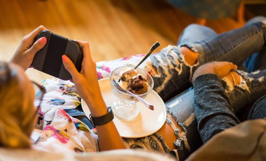 Woman with ice cream playing video game by man on sofa at home