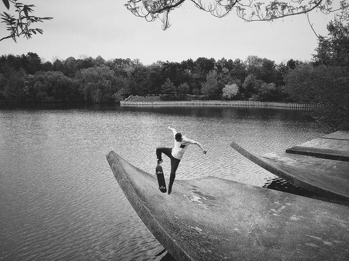 Man Skateboarding Against Lake