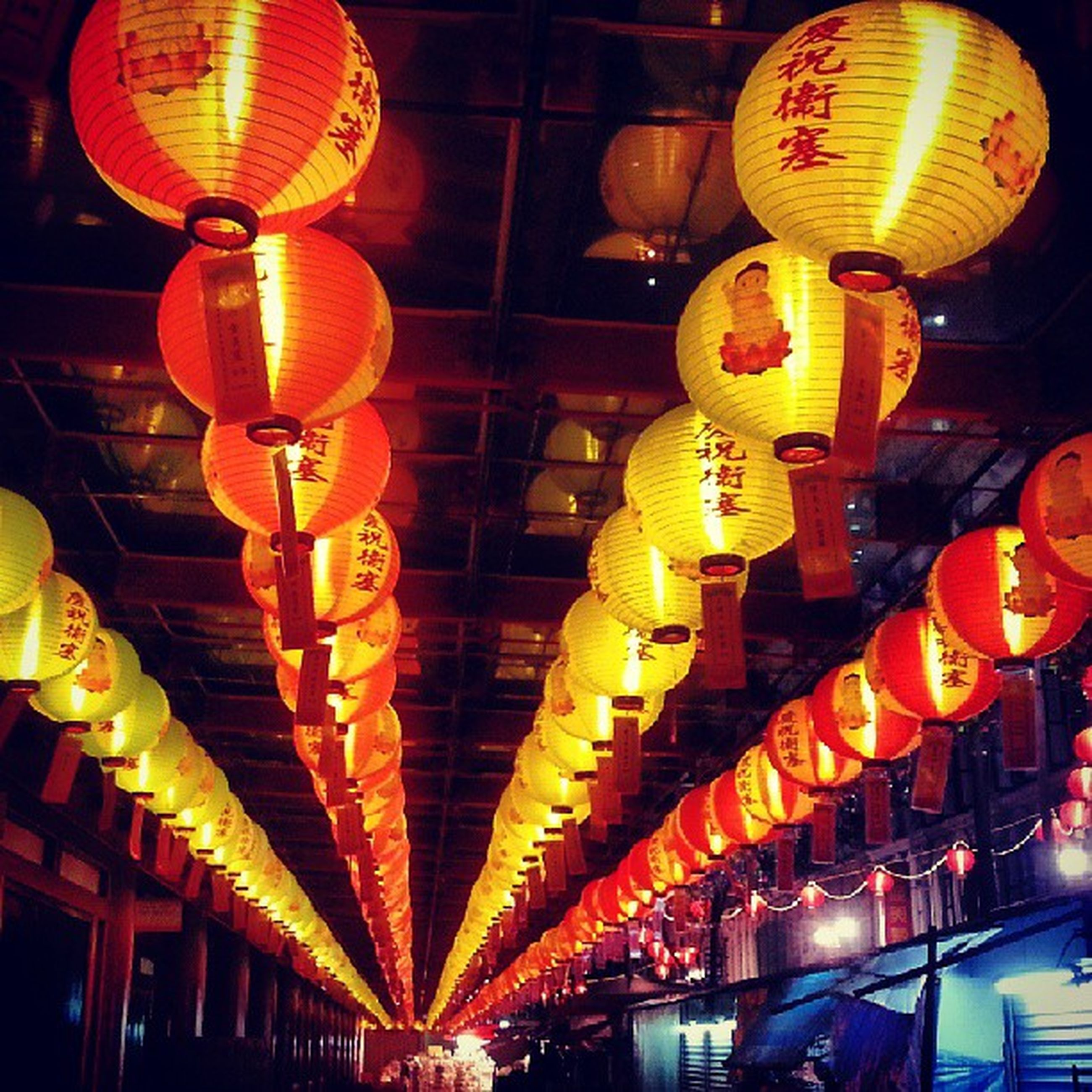 illuminated, lighting equipment, low angle view, hanging, lantern, ceiling, indoors, chinese lantern, decoration, night, in a row, architecture, built structure, electricity, culture, electric light, text, cultures, electric lamp, communication
