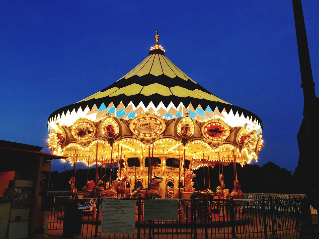 amusement park, arts culture and entertainment, carousel, clear sky, amusement park ride, low angle view, outdoors, built structure, blue, illuminated, night, no people, sky