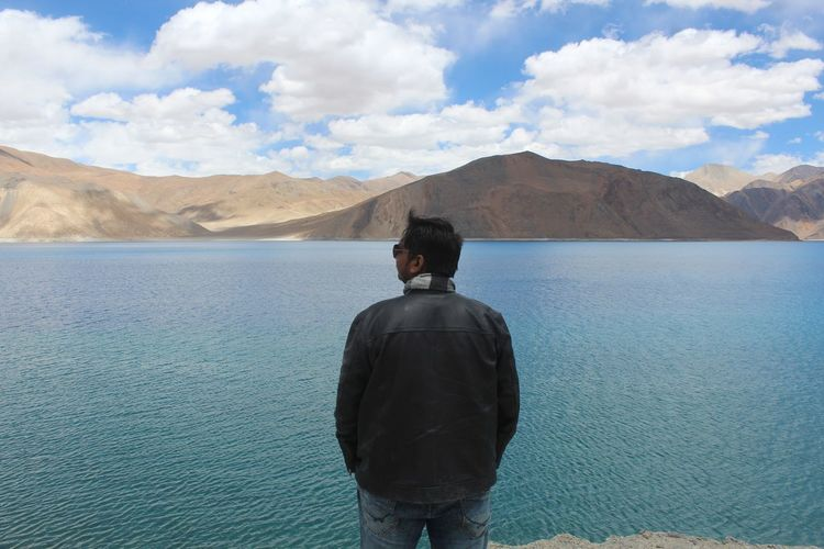 Rear view of man looking at mountains against sky while standing by lake
