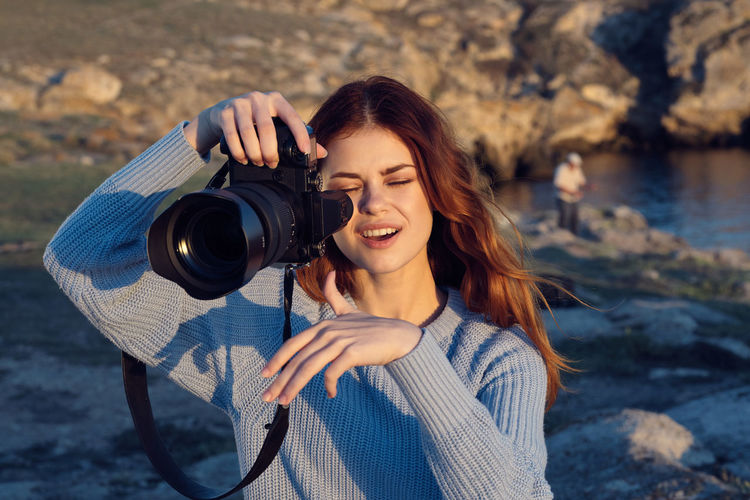 Portrait of smiling young woman photographing camera