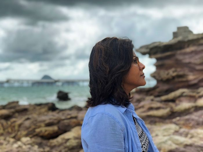 Side view of thoughtful woman standing on rocky shore against cloudy sky