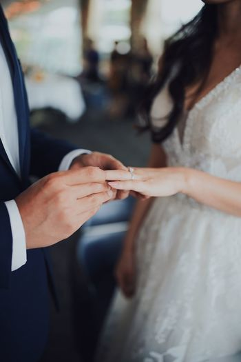 Midsection of man putting ring on bride finger during wedding ceremony