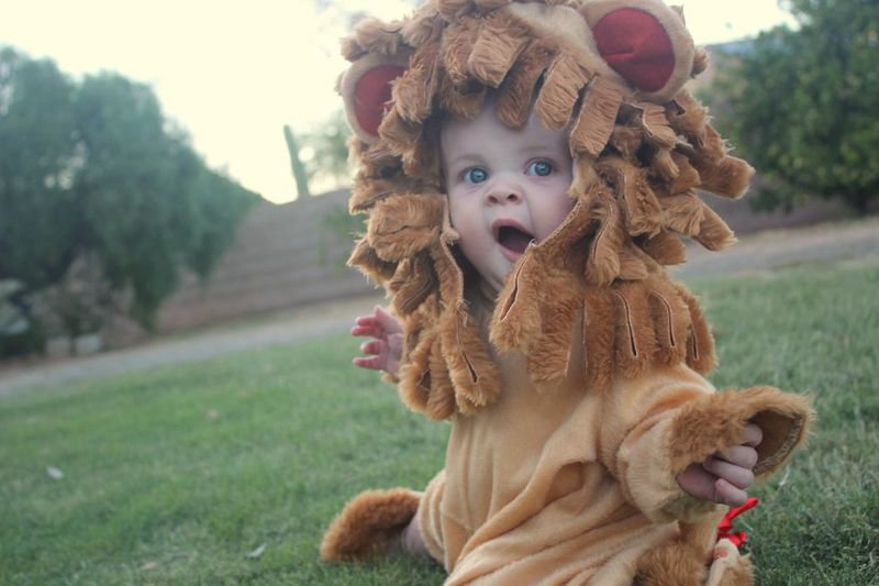 Portrait of cute baby girl wearing costume yawning in park