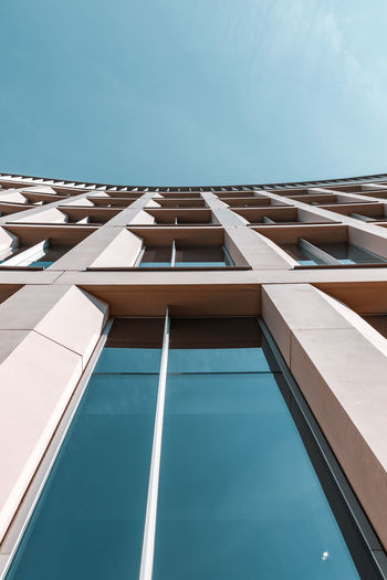 View looking up at building with tap windows against blue sky