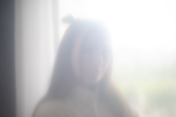 Rear view of woman standing in sunlight