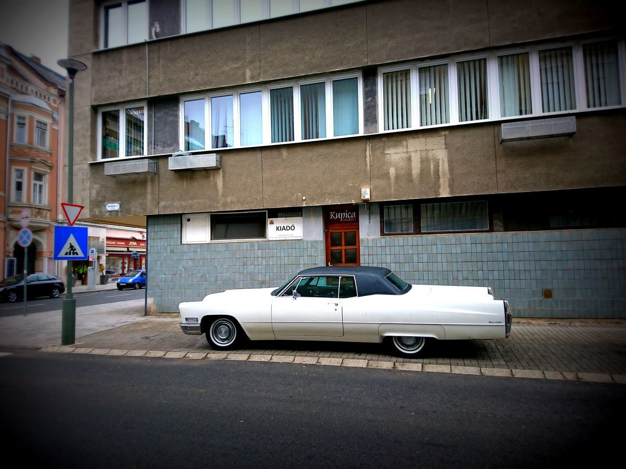 CAR PARKED ON STREET BY BUILDING