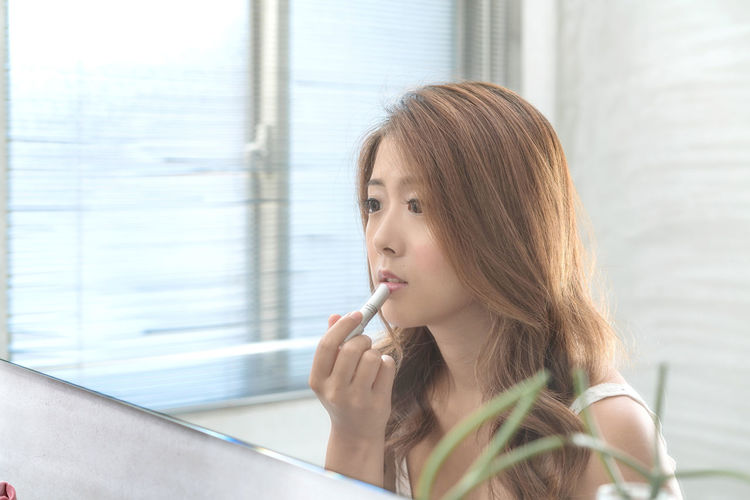 Young woman applying lipstick while looking in mirror