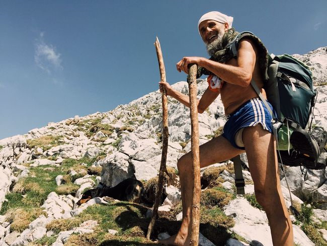 Senior Slovenian hiker, hiking barefoot with his dog at an altitude of 2000 meters, Grintovec, Slovenia, July, 2017. Grintovec Slovenia IfeelsLOVEnia Documentary Photojournalism Adventure Climbing Mountain Leisure Activity Hiking Nature Real People Dog Barefoot