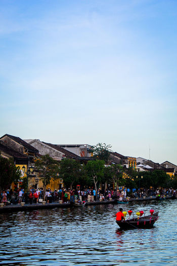 People on boats in river against sky