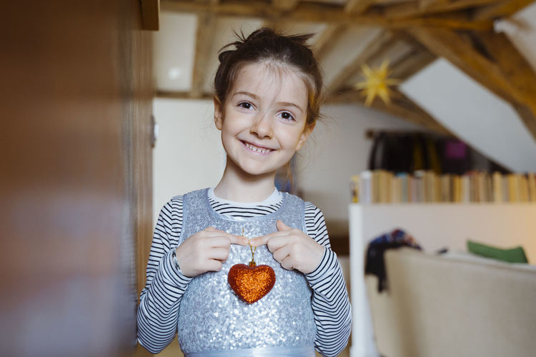 Smiling girl holding heart shape decoration at home