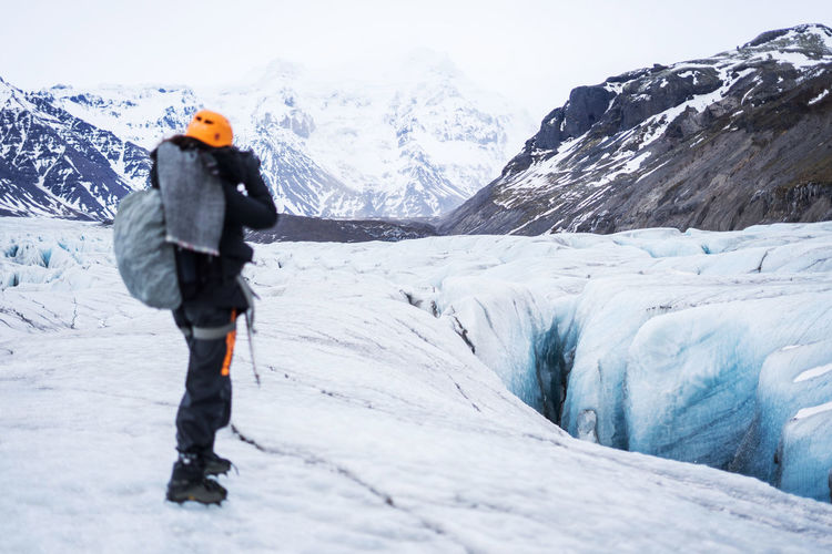 Iceland Adventure Backpack Beauty In Nature Cold Temperature Day Extreme Sports Full Length Glacier Hiking Leisure Activity Lifestyles Mountain Mountain Range Nature One Person Outdoors Real People Rear View Scenics Sky Snow Walking Warm Clothing Winter