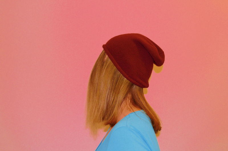 Side view of woman wearing knit hat against coral background
