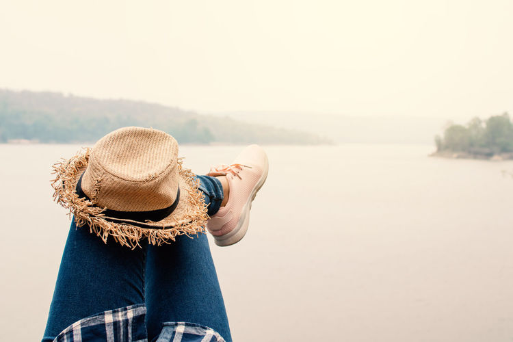 Low section of woman with hat against lake