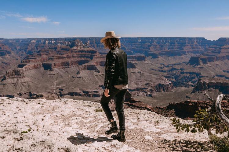 Full length of man walking on rocky mountain