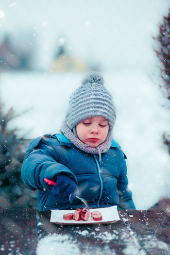 Little boy eating roasted sausage during family picnic outdoors in winter, sitting by a wooden table, wearing warm clothes, scarf and cap Winter Child Outdoors Childhood Boy Girl Cold Enjoyment Enjoy Kid Children Wintery Winter Snow Snowing Picnic Family Eating Campfire Roasting Sausage Meal Roasted person Food