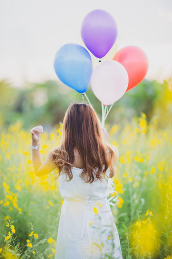 Rear view of a girl with balloons in field