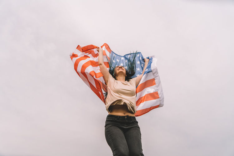 Low angel view of young woman holding american flag against sky