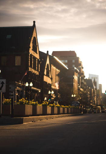 Road amidst buildings against sky at dusk