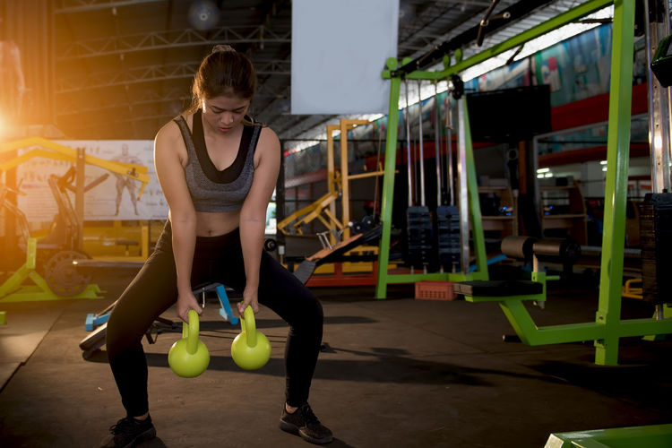 Full Length Of Young Woman Lifting Kettlebells While Standing In Gym