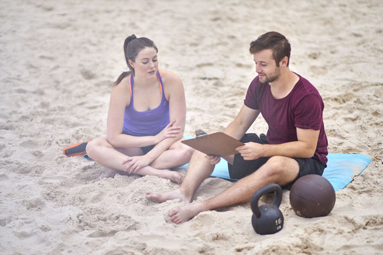 Young Woman Sitting With Fitness Instructor At Beach
