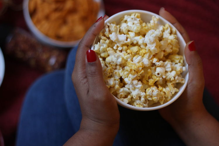 Midsection of woman holding popcorns
